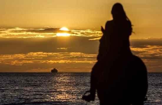 Paardrijden bij zonsondergang aan zee in El Cotillo